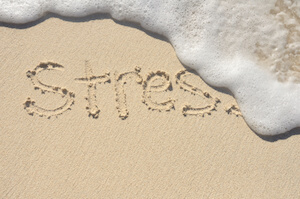 Stress written in sand with water washing it away
