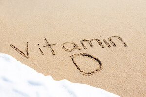 Vitamin D spelled out in the sand on the beach