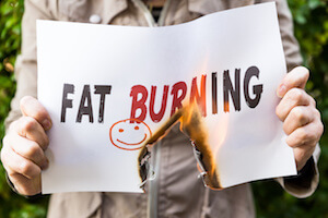 Words Fat Burning written on piece of paper thats on fire